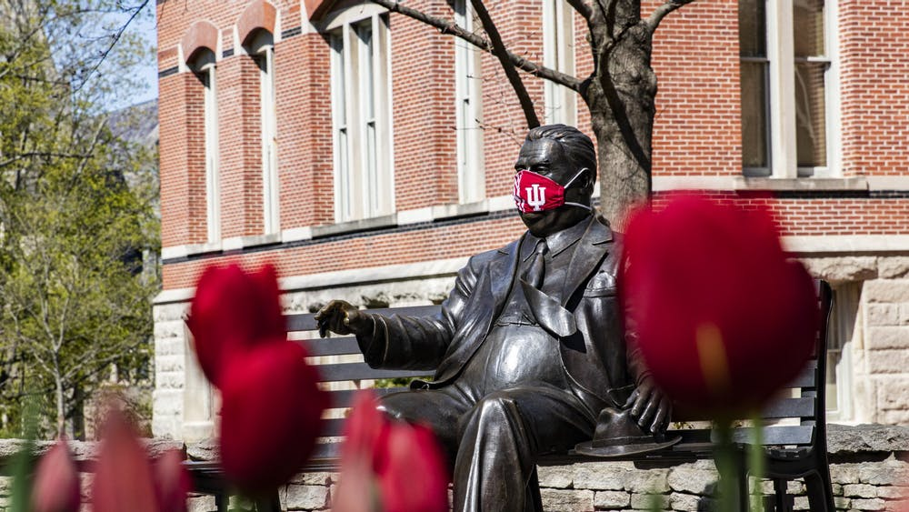 A  mask covers the face of the Herman B Wells statue April 20 on IU's campus.
