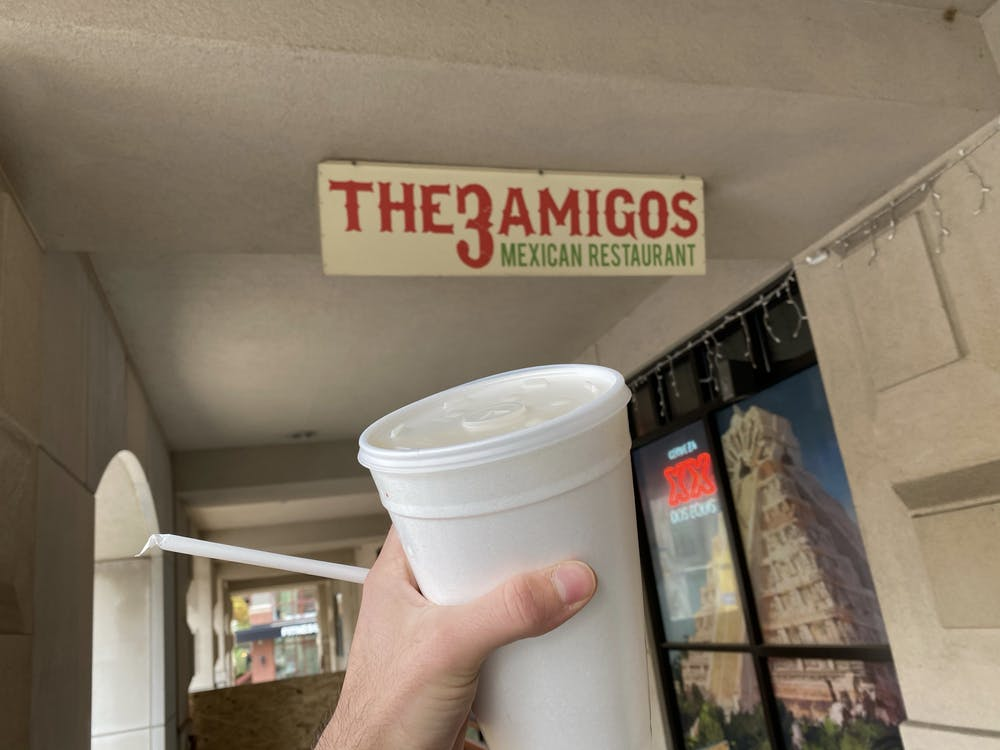 <p>IDS columnist Raul Moreno holds up a cup of horchata from the 3 Amigos outside of the College Avenue location.</p>