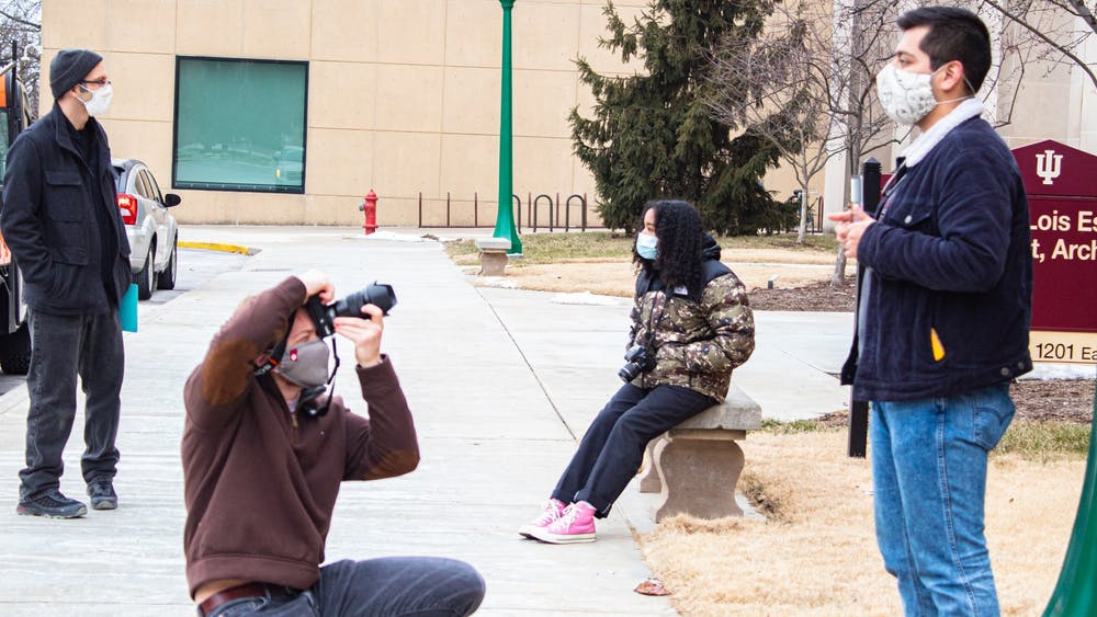 Senior Max Eslava poses as junior Tyler Richardson takes a picture for their photography class Monday outside of the IU Fine Arts Building. IU students started in-person classes Monday after having virtual classes since Jan. 19.