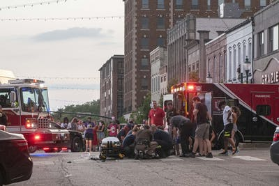 Paramedics, firefighters and law enforcement officers tend to a protester who was struck by a car July 6 just after the conclusion of the protest in downtown Bloomington. The car sped off after hitting multiple protesters and carrying them on the hood of the car before they were eventually flung off.