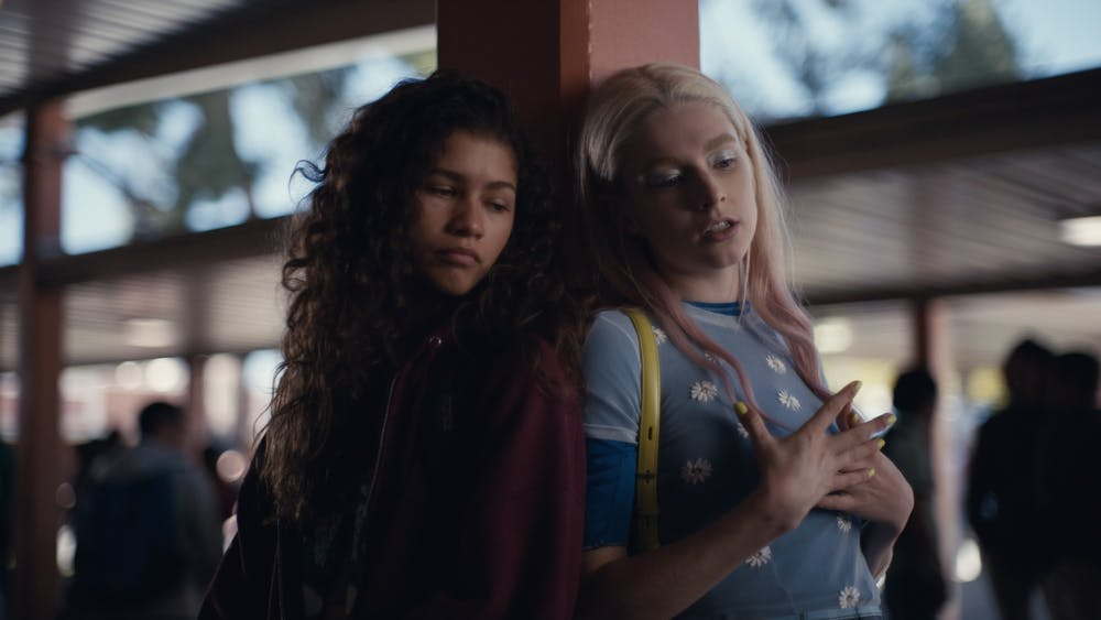 "Actresses Zendaya and Hunter Schafer lean on a beam during filming for the show ""Euphoria."" The show, which has one season released in 2019, has been releasing special one-off episodes throughout the COVID-19 pandemic focusing on individual characters like Zendaya's Rue and Schafer's Jules."