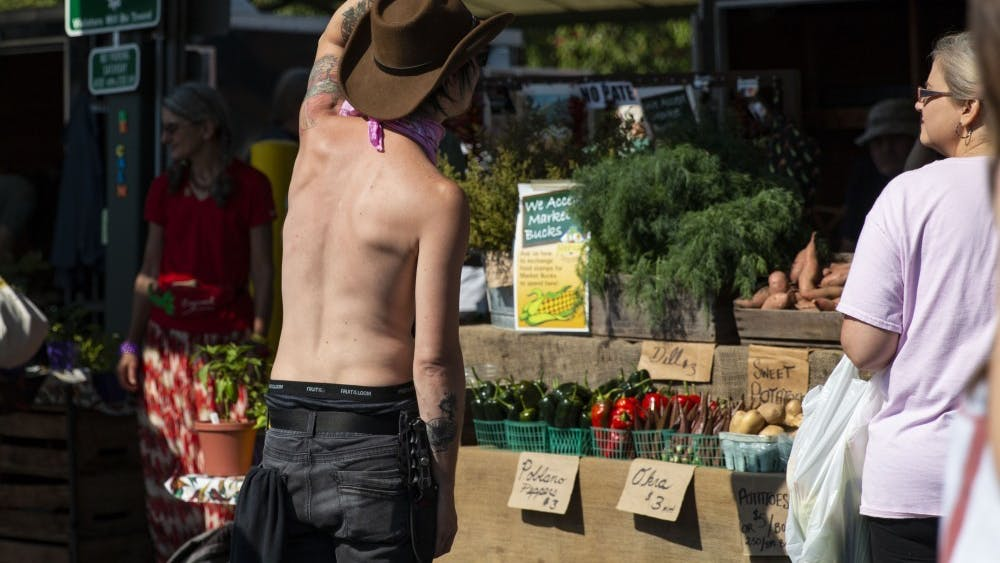 A man walks up to Schooner Creek Farm's booth to protest Sept. 28 at the Bloomington Community Farmers' Market. According to a statement on its website, the Bloomington branch of Black Lives Matter called for a boycott Wednesday of the Herald-Times and the city-run farmers' market.