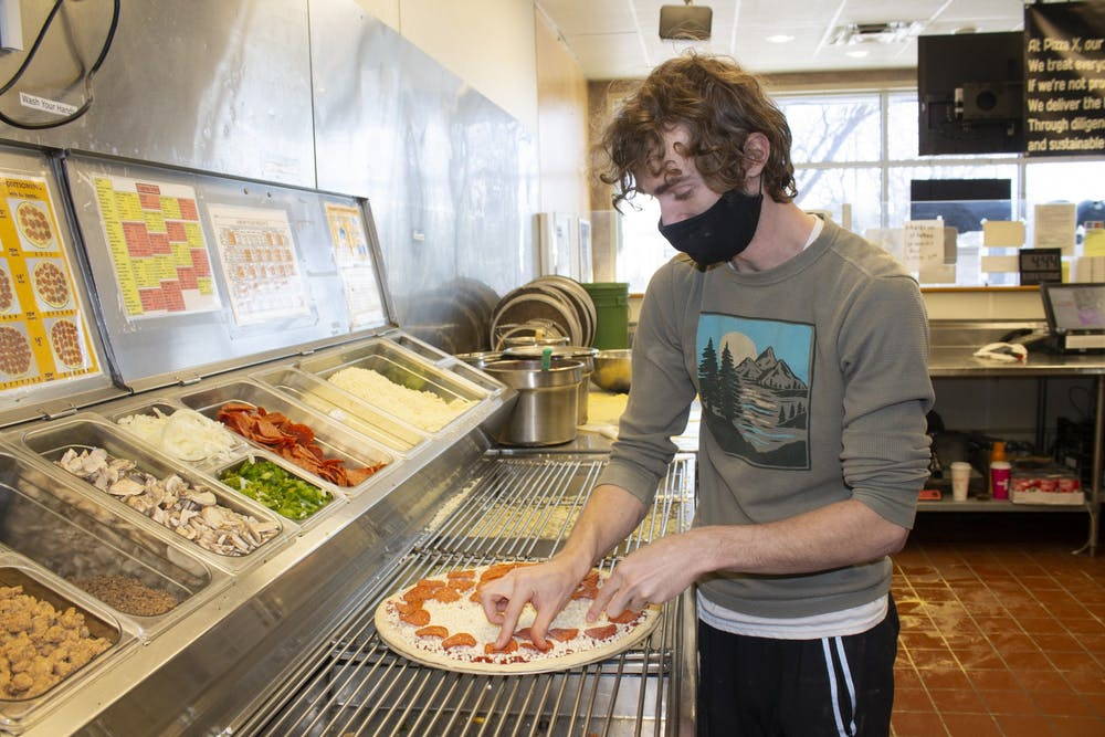<p>Second assistant manager Nik Folley designs a pizza at Pizza X West. </p>