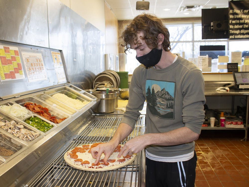 Second assistant manager Nik Folley designs a pizza at Pizza X West.