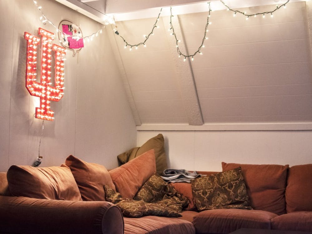 Lights and an illuminated IU sign hang in the living room of an off-campus house in Bloomington.