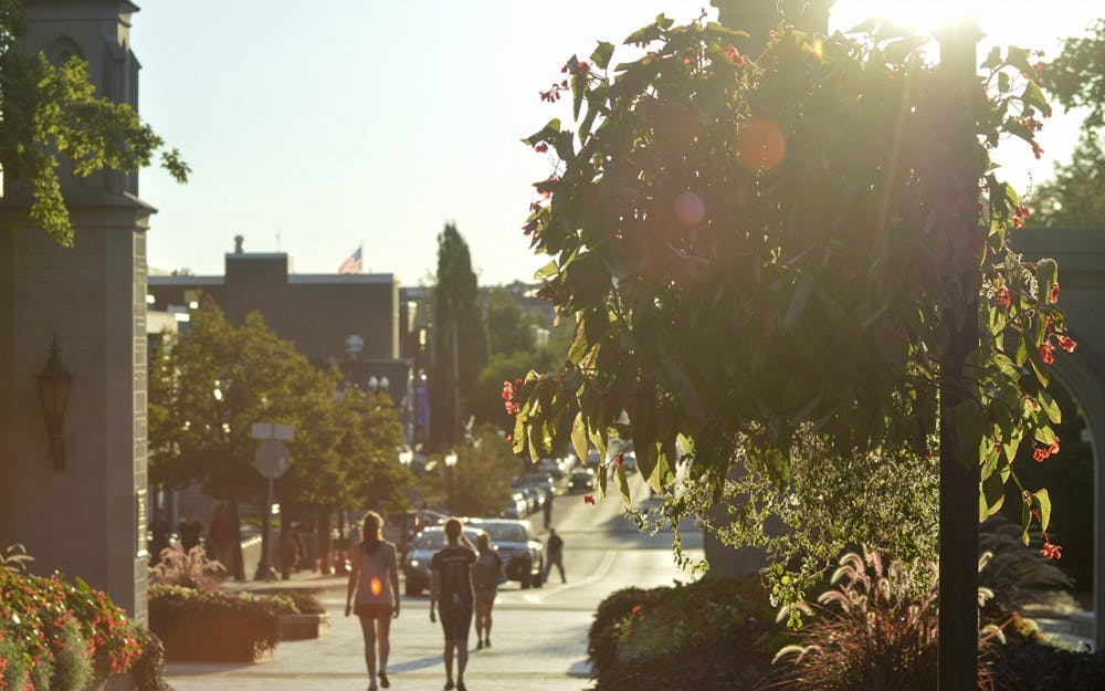 """Students prepare to exit campus as the sun begins to set on Indiana University's Sample Gates. The gates seperate Kirkwood Avenue from IUs """"Old Crescent"""" area and serve as the univeristy's most photographed structure on campus."""
