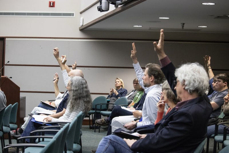Bloomington residents raise their hands April 17 during the Bloomington City Council meeting in City Hall. People were raising their hand to say they wanted to speak during public comment.