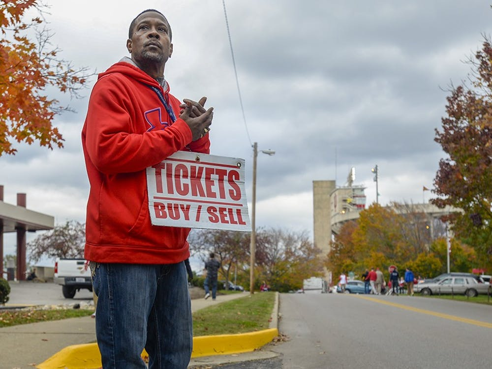 Indianapolis native Brian Stapleton, 50, awaits ticket buyers on Indiana Ave. before IU's homecoming football game against Michigan State. Stapleton, known more by his alias, Jeffery, has been scalping tickets for 18 years, and often ventures to Bloomington in hopes of making a profit, even though ticket sales for IU football are worst in the Big Ten. The ticket scalper on the street corner is a dying breed, as online sites like Stubhub and Ticketmaster are making scalping obsolete.