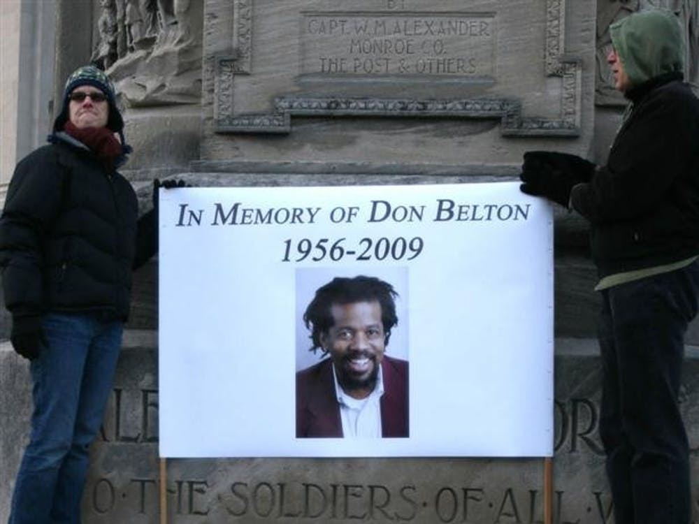 A sign is held on Bloomington's Courthouse Square during a New Year's Day 2019 memorial for assistant professor Don Belton. Belton, 54, was killed in his home by Michael Griffin, then 25, on Dec. 27, 2009.