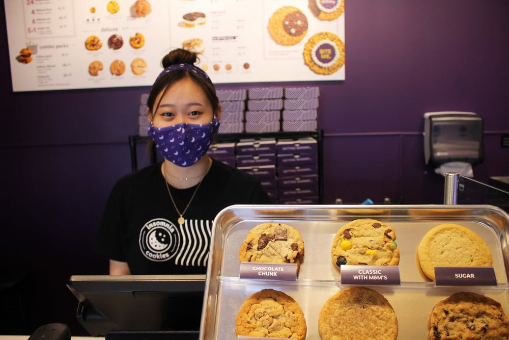 <p>IU sophomore Hannah Lim works behind the counter at Insomnia Cookies on Saturday. The store opened March 1, but celebrated its grand opening Saturday offering special deals.</p>