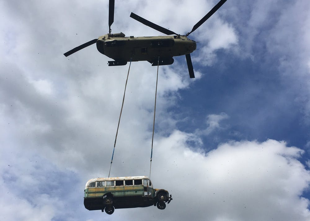 """A 1940s-era Fairbanks city bus is removed by helicopter from the remote side of the Teklanika River near Healy, Alaska. The abandoned vehicle, variously known as Bus 142, or the """"Into the Wild"""" bus, became well-known after John Krakauer's 1996 book and a 2007 movie with the same name."""