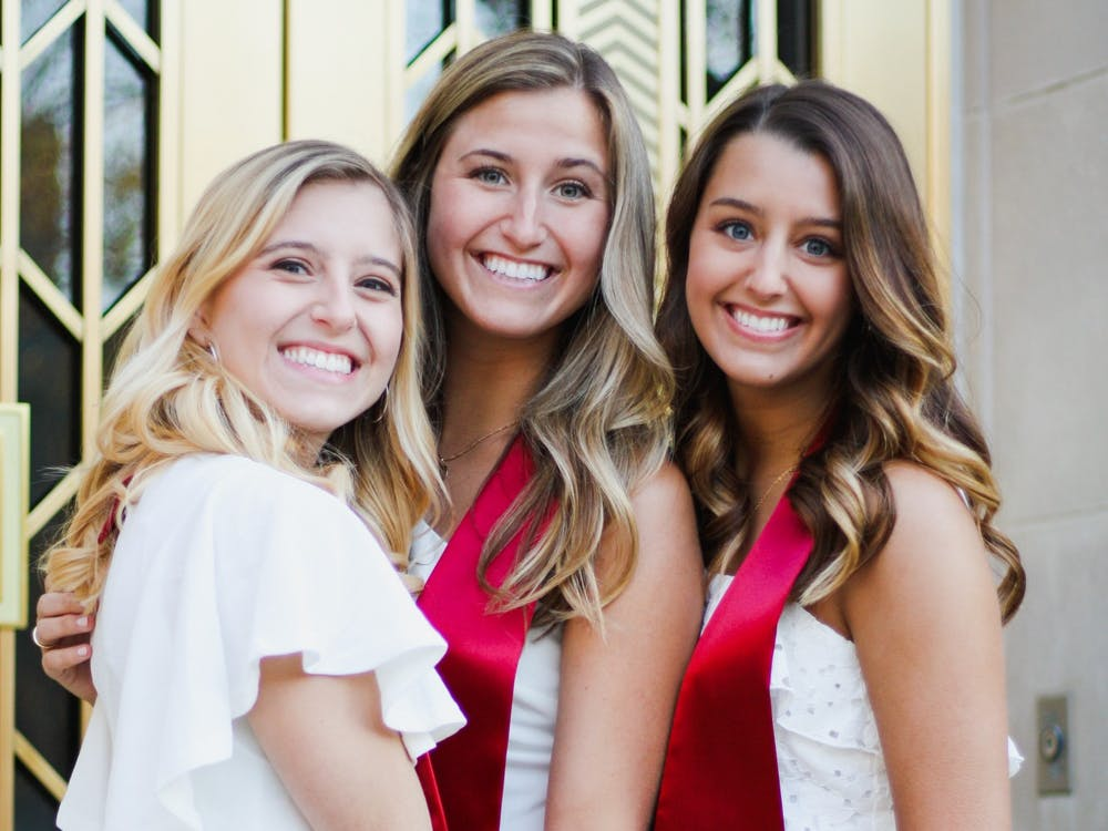Ellie, Maddie and Ronnie VanBuskirk stand for a photo on IU's campus. Ellie graduated with a degree in media, Maddie with a degree in elementary education and Ronnie graduated with a degree in kinesiology and exercise science.