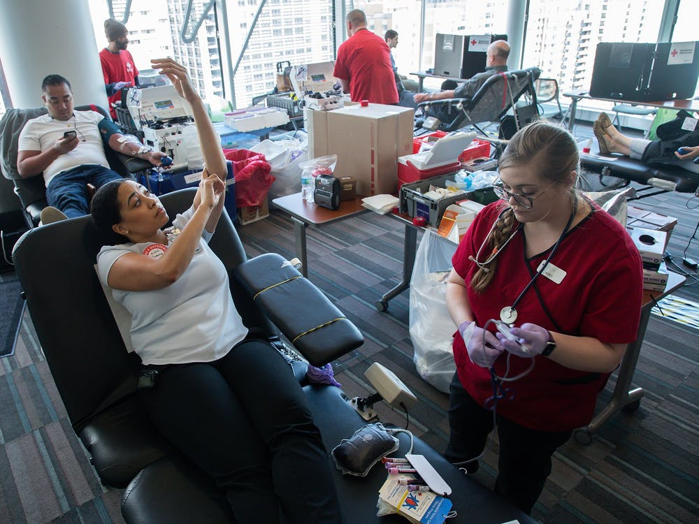 """Phlebotomist Korey Dyerly, right, puts a """"blue tag"""" on blood donated by Antonia Warren on April 2, 2019, during a Red Cross blood drive at Lurie Children's Hospital in Chicago. According to an American Red Cross statement in June, a rise in trauma cases, organ transplants and elective surgeries depleted the nation's blood inventory."""