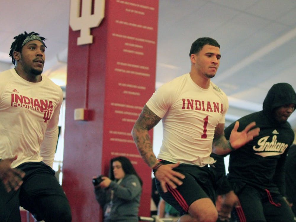 Wide receiver Simmie Cobbs Jr. participates in pre-workout stretching prior to IU football pro day Tuesday at Memorial Stadium. Cobbs was one of 11 IU football players to take part in IU pro day.