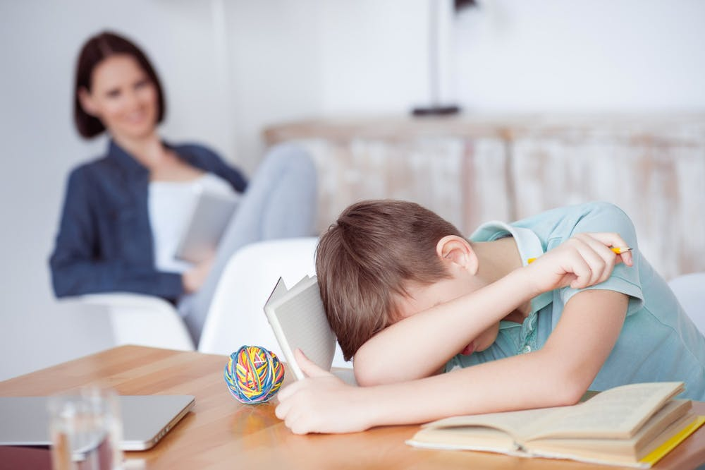 <p>A child rests his head on his arm while doing homework.</p>