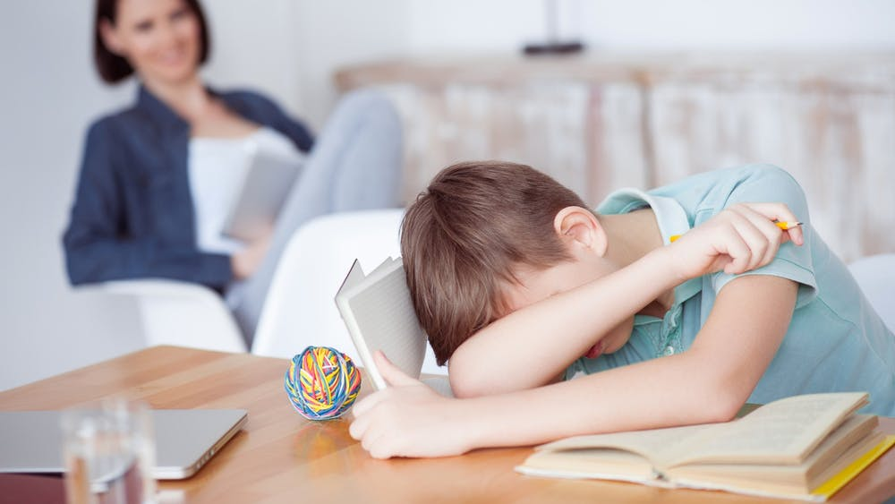 A child rests his head on his arm while doing homework.