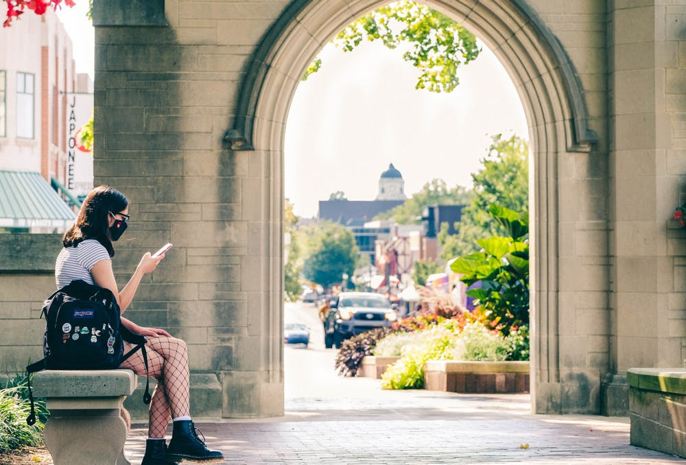 <p>Freshman Brooklynn Zabel looks at her phone while waiting for her friend Aug. 24 at the Sample Gates.</p>