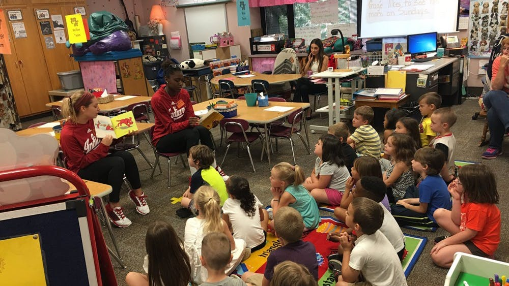 Sophomore Samantha Fogg (left) and senior Jazzmine McDonald read to a class during IU volleyball's Sept. 16 visit to Templeton Elementary