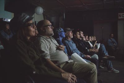 Patrons of a Cicada Cinema film event watch a film. Cicada Cinema is a pop-up cinema collective based in Bloomington.