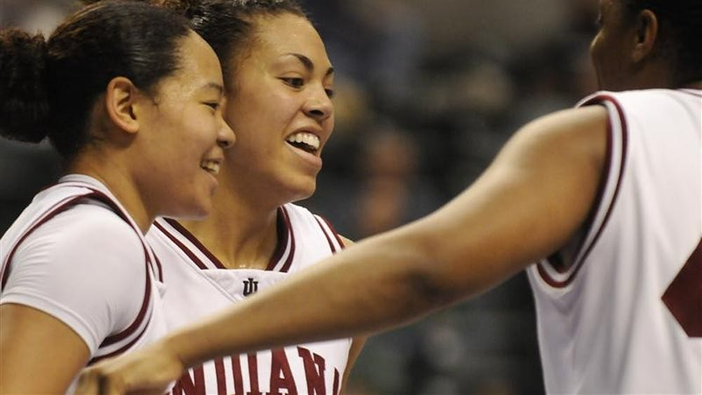 IU seniors Kim Roberson, left, Whitney Thomas and Amber Jackson share a laugh during the closing minutes of IU's 68-50 win against Michigan in the first round of the Big Ten Tournament on Thursday at Conseco Fieldhouse in Indianapolis.