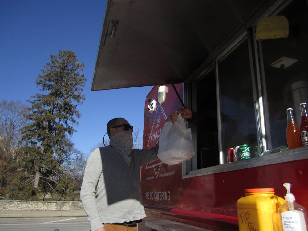 Brown County resident Jacob Ebel receives food from the La Poblana food truck parked in the TIS parking lot Jan. 19. La Poblana is one of many food trucks in Bloomington whose sales drop during the winter months.