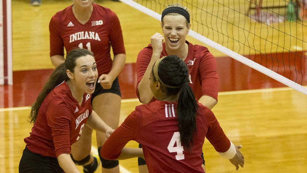 Members of the volleyball team celebrate during their game against Penn State on Oct. 18 at University Gym.