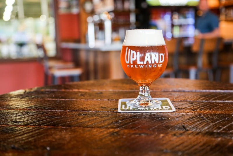A glass of beer sits on a table in Upland Brewing Company. The restaurant announced its 2019 beer lineup on Jan. 9, including two new IPAs and a winter seasonal beer to be debuted later in the year.