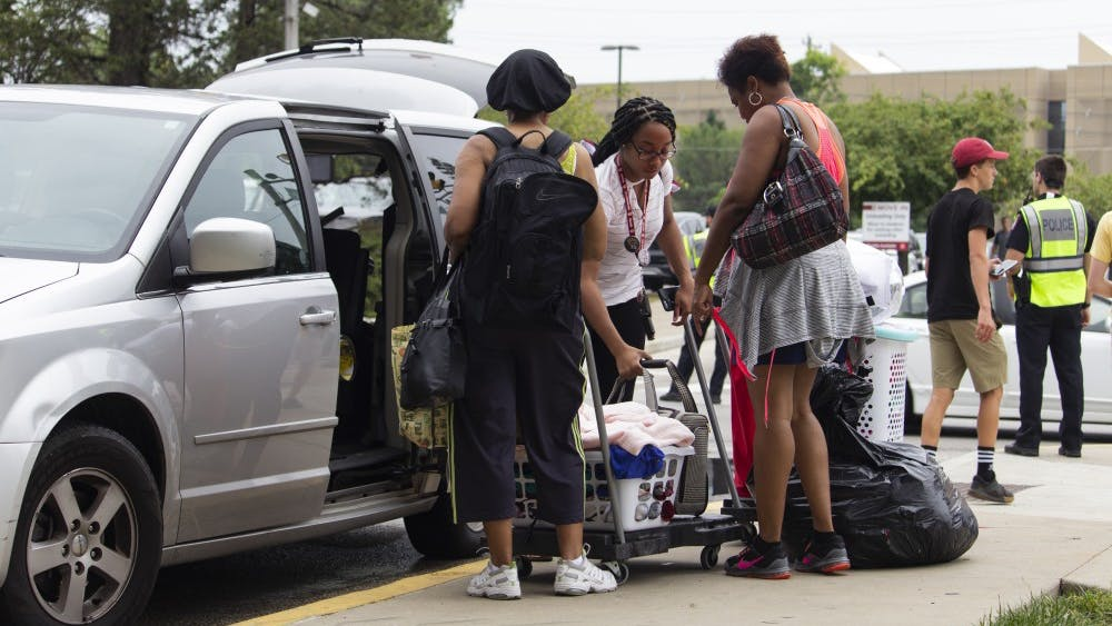 Family members help move their student's belongings into Teter Quadrangle during move-in week.
