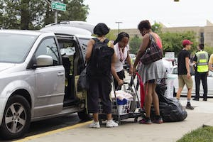 Family members help move their student's belongings into Teter Quad during move-in week. As a record number of new students settle into dorm life, some are left to temporarily live in the lounge spaces of their floors.