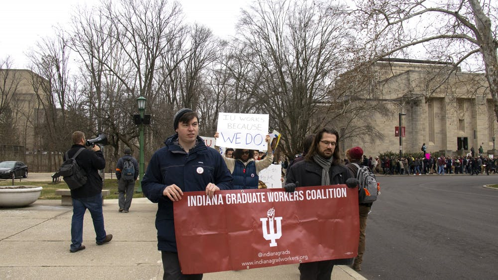 Participants walk Jan. 28 to Herman B Wells Library during a graduate student march.