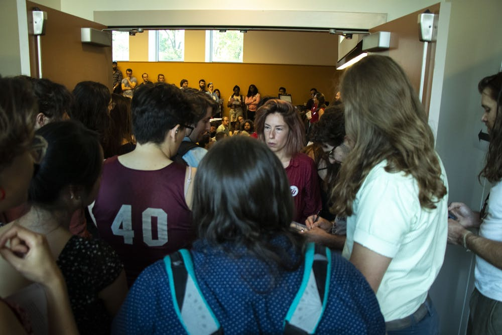 <p>Students listen from the hallway at the Indiana University Graduate Workers Coalition town hall meeting Sept. 12 at the Lee Norvelle Theatre and Drama Center. Indiana Graduate Workers Coalition, a student-led organization protesting conditions for IU graduate students, organized the event.</p>