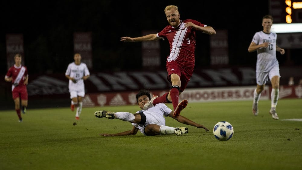 Senior Simon Waever leaps over an opponent and chases after the ball Sept. 27 at Bill Armstrong Stadium. IU will play No. 19 the University of Kentucky on Wednesday.