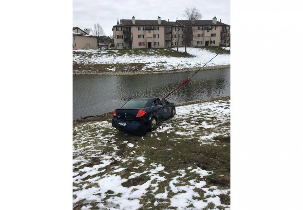 The Indianapolis Fire Department pulls a navy-blue Pontiac G6 out of a retention pond. Anthony Burgess Jr. died Sunday after saving his three-year-old daughter from their sinking car, which fell into the retention pond at the Core Riverbend apartments after his daughter had accidentally bumped the gear shift when climbing into the front seat.