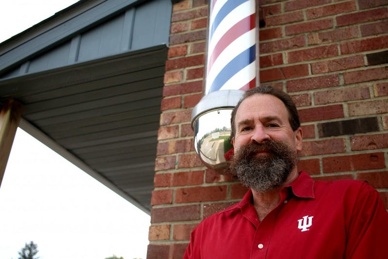 Frank Meadows stands outside Bill's Barber Shop on Oct. 12. Meadows has been cutting Hoosiers' hair for more than 30 years, including that of IU President Michael McRobbie.