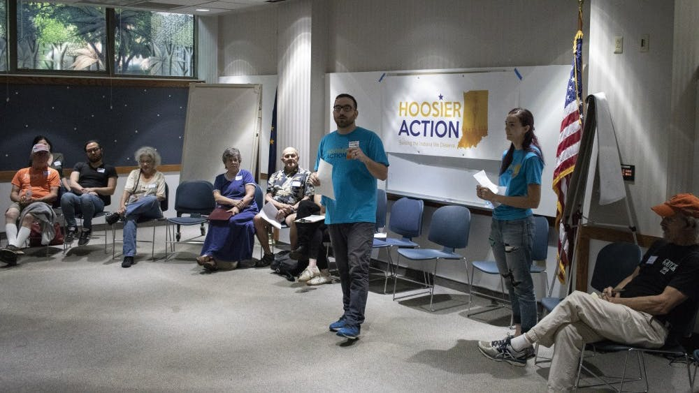 """Organizer for Hoosier Action Will Stauffer talks to attendees of Save Hoosier Healthcare Campaign Kickoff on May 29 in the Monroe County Public Library. """"We need everybody in the fight,"""" he said."""