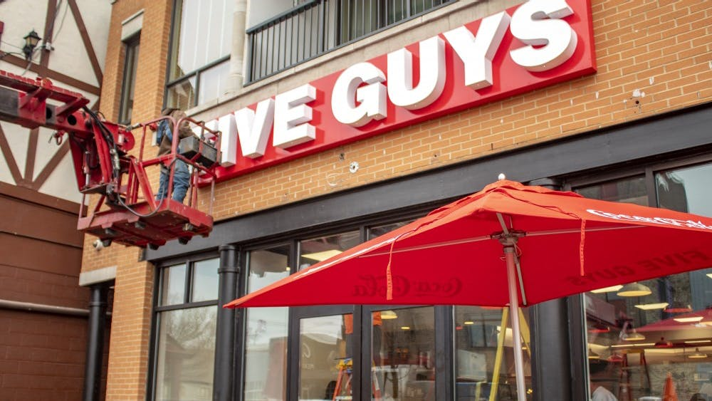 Construction workers attach the Five Guys sign to the building Nov. 29 on Kirkwood Avenue. The restaurant is set to open Dec. 4.