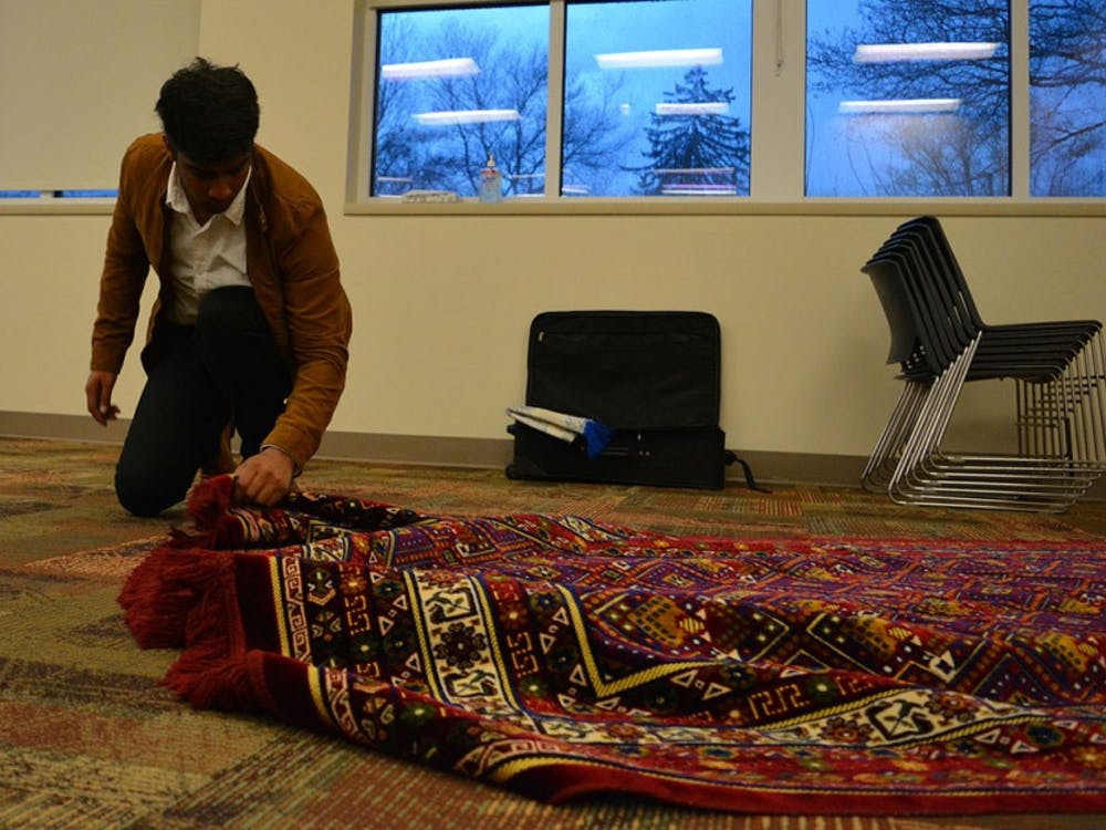 """Sophomore Faadil Shariff lays down prayer rugs before the """"Taste of Islam"""" banquet Thursday night. """"Taste of Islam"""" is the fourth of five events for the Muslim Student Association's Islam Awareness Week."""
