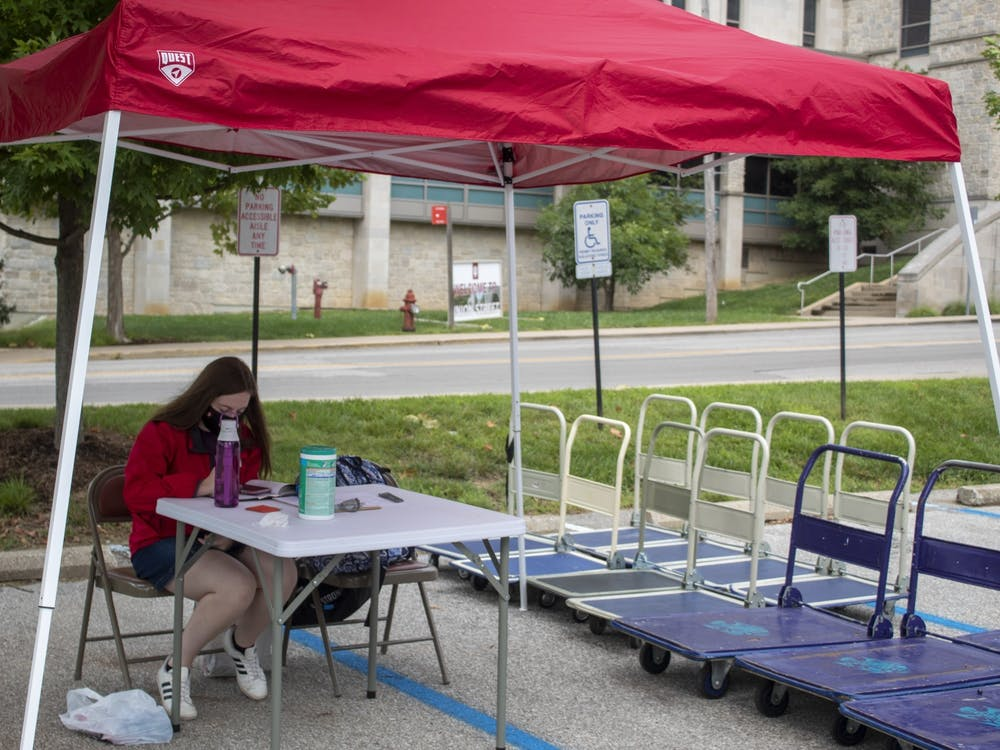 Residential assistant Jada Collins runs the cart sign-out station Aug. 18 outside of Eigenmann Hall. IU Student Association passed a bill paying residential assistants' and CommUNITY educators' hazard pay.