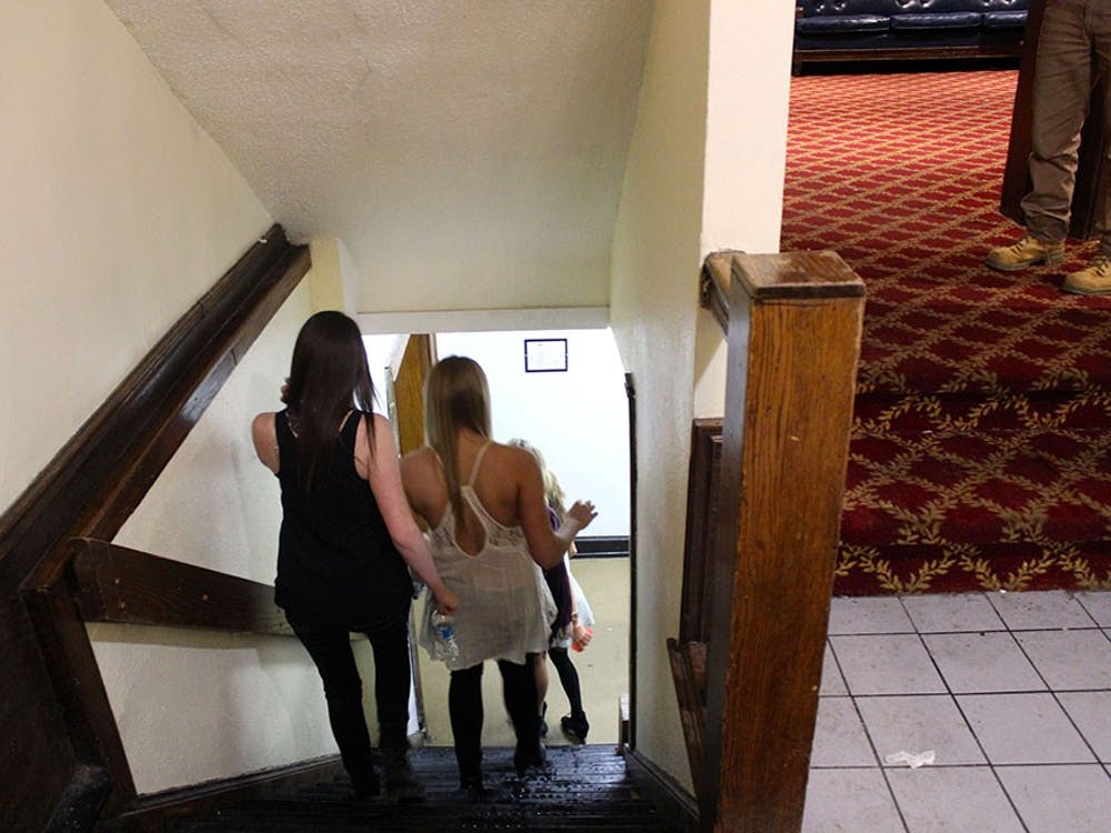 A group of girls walk down the stairs to a party at the Alpha Tau Omega house on a Saturday night in February. The stairs were wet from the snow, and pledges had to dry them off to keep people from slipping.