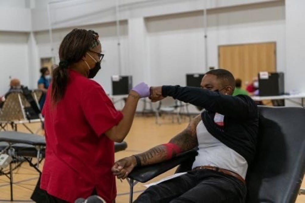 <p>A man fist bumps a blood drive worker after donating blood. The American Red Cross is coordinating a blood drive during February, which is Black History Month .</p>