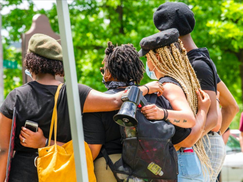 """Organizers of the """"Enough is Enough"""" protest gather on stage June 5 , 2020, in Dunn Meadow. The protest came after the May 25, 2020, killing of George Floyd by a Minneapolis Police Department office."""