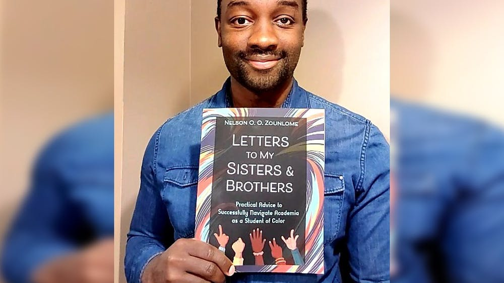 "IU graduate student Nelson Zounlome poses for a photo with his book, ""Letters to My Sisters and Brothers: Practical Advice to Successfully Navigate Academia as a Student of Color."" He began writing his book about two years ago to create a resource for Black, Indigenous and other students of color."