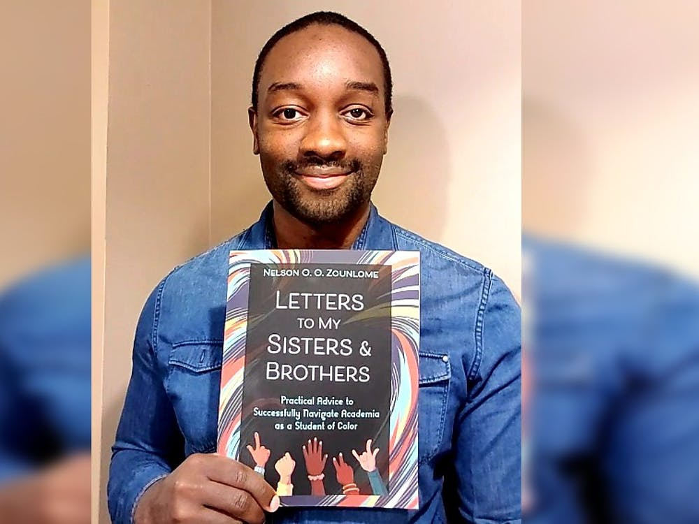 """IU graduate student Nelson Zounlome poses for a photo with his book, """"Letters to My Sisters and Brothers: Practical Advice to Successfully Navigate Academia as a Student of Color."""" He began writing his book about two years ago to create a resource for Black, Indigenous and other students of color."""