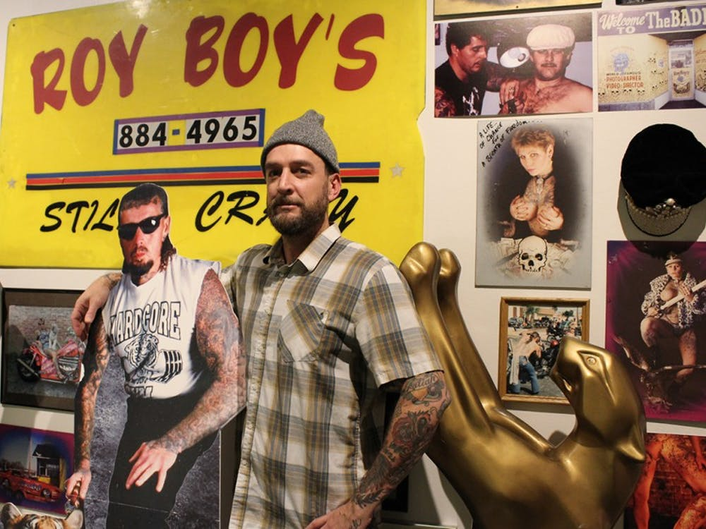Tattoo exhibit curator Jeremy Sweet poses next to a cardboard cutout of Roy Craig Cooper, nicknamed Roy Boy, who was one of the most iconic tattooers in Indiana. One section of the Grunwald Gallery's newest exhibit focuses on Roy Boy as a tattoo artist.