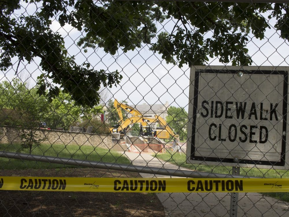 A sign indicating a closed sidewalk stands Monday, May 21, outside the Indiana Memorial Union. Since the summer started, IU has undertaken numerous construction projects around campus.