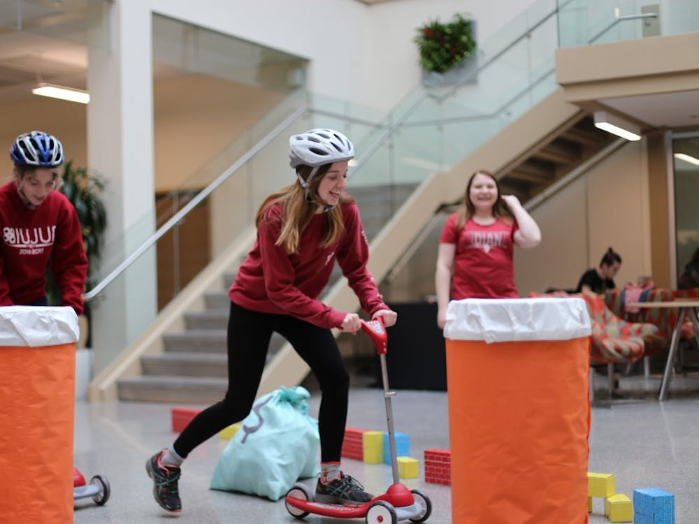"""Junior Elli Schank and senior Sarah Addison ride scooters through an obstacle course at """"Race for More than Four."""" The event was organized by Public Relations Student Society of America to raise awareness for childhood cancer treatment."""