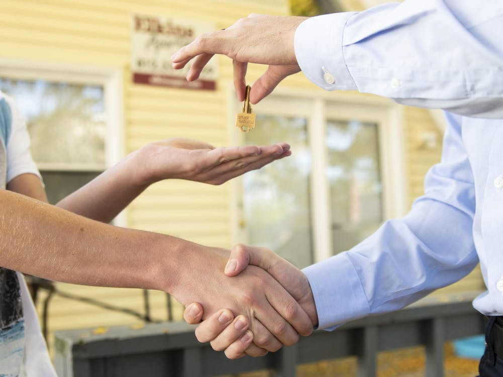 An agent from a rental company hands over the key to an off-campus property in Bloomington. There are several different leasing companies in Bloomington.
