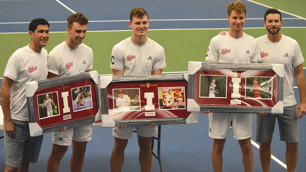 IU men's tennis head coach Jeremy Wurtzman, graduate student William Piekarsky, senior Andrew Redding, graduate student Bennett Crane and assistant coach Mike Murray pose Sunday at the IU Tennis Center. The three seniors were honored with awards Sunday.