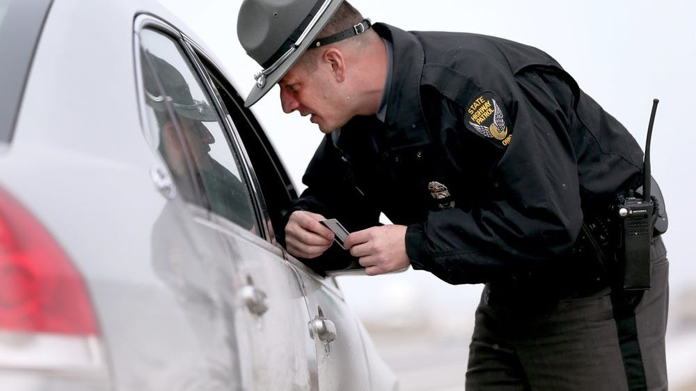 "Ohio Highway Patrol trooper John Williams speaks to a driver he pulled over for speeding Jan. 20 on the Ohio Turnpike. Indiana State Police will launch an initiative called ""Full Court Press"" in March that aims to crack down on speeding."