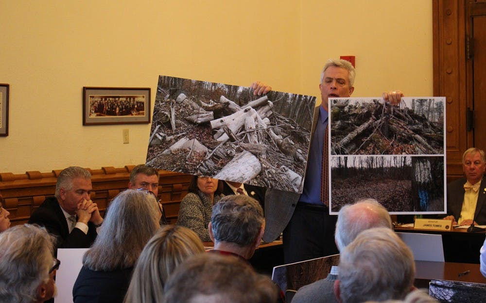 Jeff Stant, executive director of the Indiana Forest Alliance holds up posters depicting clearcuts. Stant testified in support of Senate Bill 420 at the Monday morning hearing.